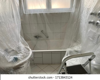 covered bathroom walls with tarp and ladder in preparation for painting - house renovation concept