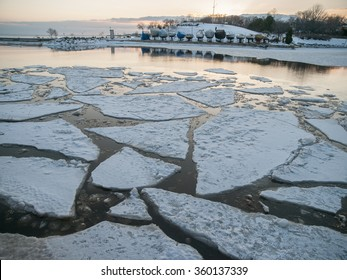 Covered boats on Lake Ontario with floating ice chunks and snow, in Oakville, Ontario, Canada in winter.