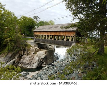 covered bridge with water and rocks or stones in Canada