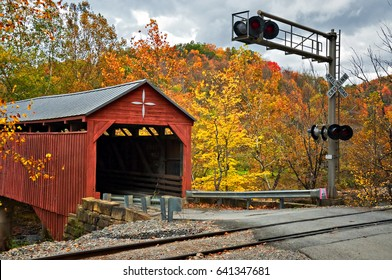 Covered Bridge WV A red covered bridge in West Virginia awaits a car or a train to pass on the nearby tracks. Autumn colored trees fill the scene. A railroad crossing light warns of oncoming trains.