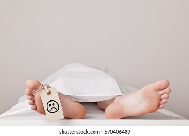 Covered dead body of a person in the morgue with a tag attached to the toe