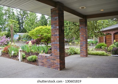 Covered entrance front porch with front yard in spring landscape.