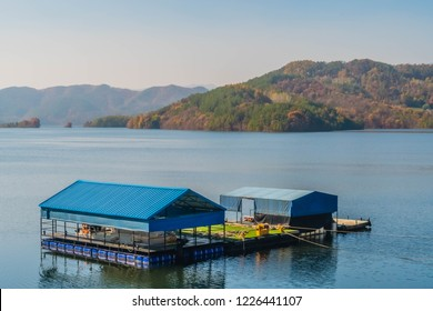Covered floating boat dock in calm lake on autumn day with trees in fall colors in background.