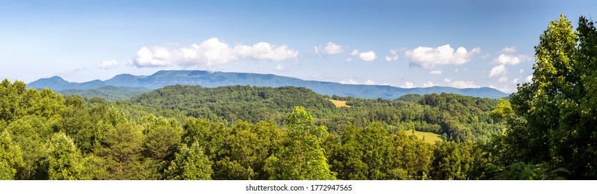 Covered in green forest and topped by a cloudy blue sky, the Smoky Mountains of Tennessee are viewed from an overlook on the Foothills Parkway.