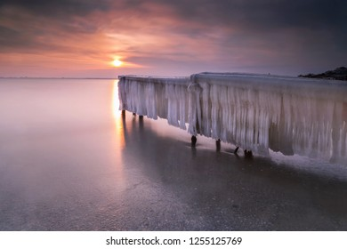 Covered with ice pier in winter at sunset