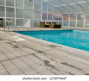 Covered Indoor Swimming Pool With Poolside Furniture Surrounded By Wooden Decking  Providing Ad Space