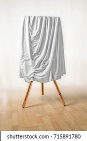 covered painting on an easel, white cloth over the picture, wooden floor and light background, art concept for an exhibition opening day or a presentation ceremony, soft focus, copy space