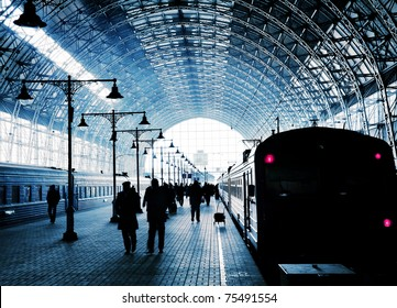 Covered railway station with trains and silhouettes of hurrying people