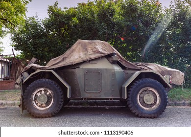 Covered vintage old military vehicle parking on street