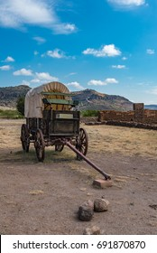 Covered wagon with green buck board next to ruins on Fort Davis military post