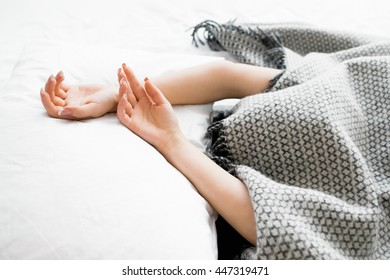 Covered woman with protruding hands out of blanket. Female hands on white sheet, woman under gray blanket. Frozen woman hiding under gray blanket