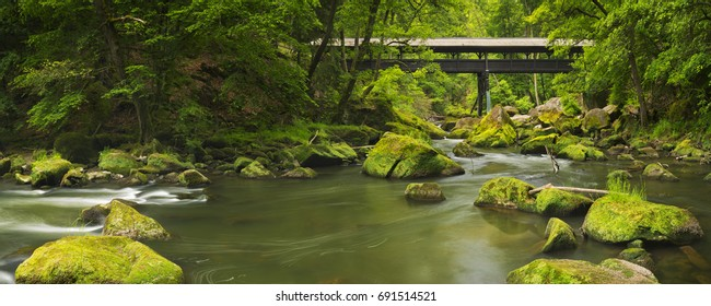 A covered wooden bridge over a river in lush forest near Irrel, Germany.