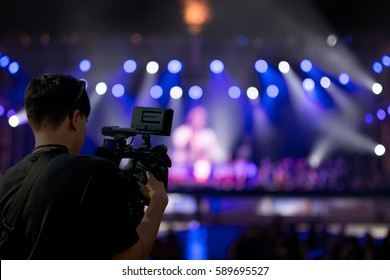 Covering an event on stage with a video camera.
