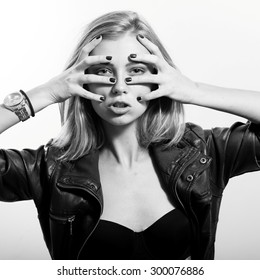 covering face and looking at camera sexy young blonde woman posing emotionally over light copy space background, black and white portrait