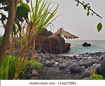 a coveted and idyllic bay with dark gray stone and pebble beach, a few green plants grow up to the water, a small parasol made of raffia stands lonely right on the water. La Palma, Canary Island.