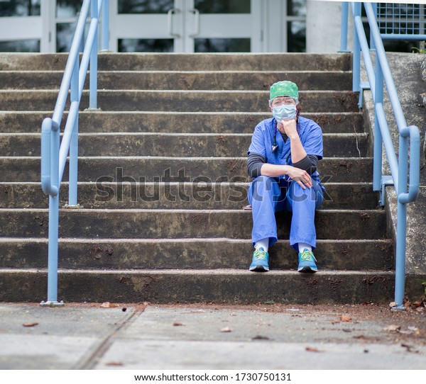 COVID 19 nurse sitting on the hospital steps wearing blue scrubs and PPE, eye shield, mask and cap.