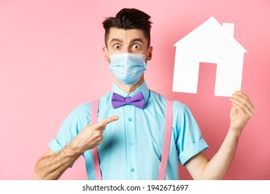 Covid, pandemic and real estate concept. Amazed man in face mask pointing at paper house cutout, standing impressed on pink background