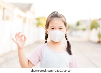 Covid-19 and Air pollution pm2.5 concept.Little chinese girl wearing mask for protect pm2.5 and OK finger hands gesture for stop corona virus outbreak.Wuhan coronavirus and epidemic virus symptoms. - Shutterstock ID 1630142419