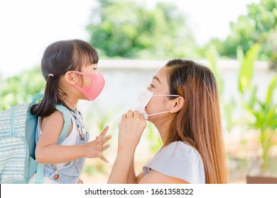 Covid-19 and Air pollution pm2.5 concept.Little chinese girl and chinese mother holding her kid wearing mask for protect pm2.5 in the garden at home.Covid-19 coronavirus and epidemic virus symptoms.