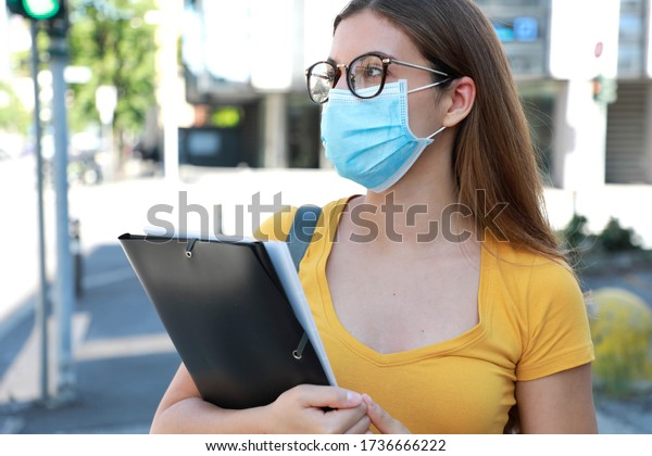 COVID-19 Beautiful University Student Female with Surgical Mask Walking in City Street. College Girl Back to School during Pandemic Coronavirus Disease 2019.