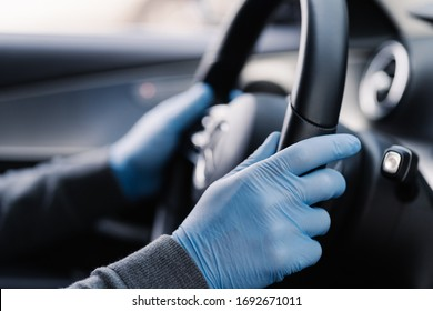 Covid-19 concept. Man drives in car, wears medical gloves, protects himself from bacteria and virus, holds car steering wheel. Coronavirus protection. Transport, quarantine and corona disease.