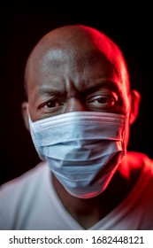 COVID-19, concerned black man with protective mask, looking at the camera. Coronavirus concept. Studio shot with red light on dark background. Selective focus.