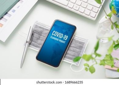 COVID-19 or Corona virus ECONOMIC IMPACT background concept. Mockup mobile phone for Covid 19 business impact with facial masks and Alcohol Mini Hand Sanitizer gel on working office desk table.