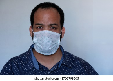 Covid-19 Corona virus pandemic facemask personal protective equipment mask mixed race male with beard wearing blue shirt confused expression face