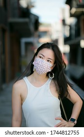COVID-19  Coronavirus  Asian woman in city street wearing face mask protective for spreading of disease virus or woman wearing face mask because of air pollution.