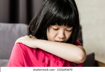Covid-19 or coronavirus concept. Asia girl child coughing as allergy from air pollution. Asian kid tuck her elbow and arm to cover her mouth to reduce virus germs  to spread from cough when sick