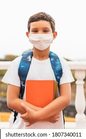 COVID-19 coronavirus concept. School with a medical mask to protect the health of the influenza virus. Student girl with backpack and books - outdoor portrait. The boy goes back to school.