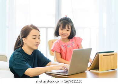 Covid-19 Coronavirus and Learning from home, Home school kid concept.Little asian girl study with online learning and asian mother work from home with laptop.Quarantine and Social distancing concept.