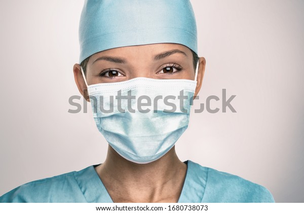 COVID-19 Coronavirus pandemic happy Asian doctor positive with hope wearing surgical mask and blue protective scrubs at hospital. Inspiring confidence in the future to solve the crisis.