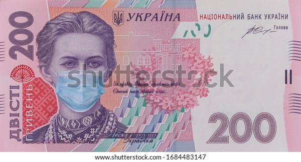 COVID-19 coronavirus in Ukraine. 200 hryvnia banknote with Lesya Ukrainka in a medical mask. Global financial and economic crisis has affected Ukraine. Ukrainian money, coronavirus concept, montage