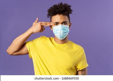 Covid19, Gesundheitswesen und Medizin Konzept. Nahaufnahme eines Porträts von ernstem hispanischen Kerl in medizinischer Maske, mit Pistole am Kopf, als ob krank und müde von Menschen nicht vermeiden sozialen Kontakt, violetter Hintergrund