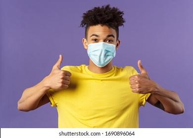 Covid19, Gesundheitswesen und Medizin Konzept. Begeisterter, glücklicher spanischer Kerl in Gesichtsmaske, zeigen Daumen hoch und lächeln mit Augen, aufgeregt, unterstützen soziale Distanzierung, vorbereitet für den Einkaufen-Einkaufen