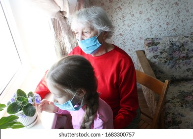 The Covid-19, health, safety and pandemic concept - senior old woman and teen girl wearing protective medical mask sitting near the window at home for protection from virus