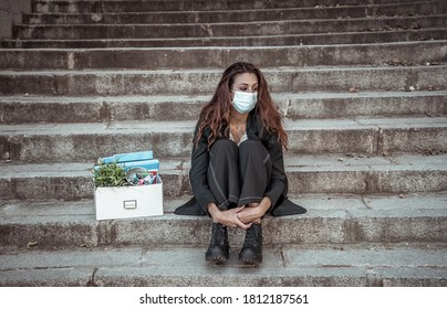 COVID-19 lay off and unemployment. Depressed business woman with face mask outside office with personal staff box feeling hopeless after losing job due to redundancy amid Coronavirus job cuts.