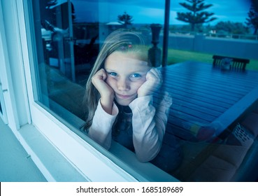COVID-19 Lockdowns. Depressed and lonely little girl looking through the window during quarantine. Child feeling sad as coronavirusu pandemic forces families to stay home in self isolation. - Shutterstock ID 1685189689