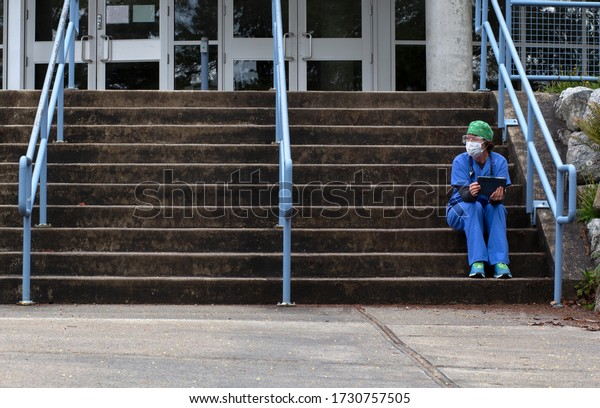 COVID-19 nurse sitting on the hospital steps on her break wearing PPE, blue scrubs, face mask, glasses and cap.