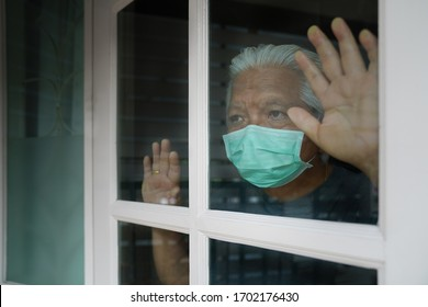 COVID-19. old man looking through the window and wearing mask protection. Patient isolated to prevent infection at home. Pandemic. Quarantine