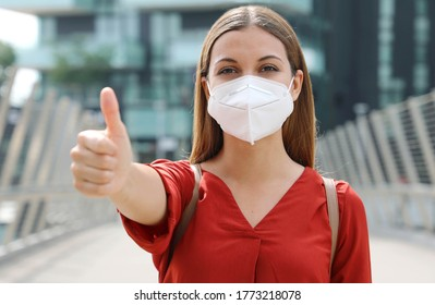 COVID-19 Optimistic business woman wearing protective mask KN95 FFP2  showing thumbs up in modern city street
