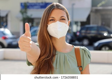 COVID-19 Optimistic young woman wearing protective mask KN95 FFP2 avoiding Coronavirus disease 2019 showing thumbs up in city street