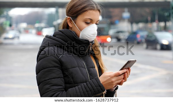 COVID-19 Pandemic Coronavirus Mobile Application - Young Woman Wearing Face Mask Using Smart Phone App in City Street to Aid Contact Tracing in Response to the 2019-20 Coronavirus Pandemic