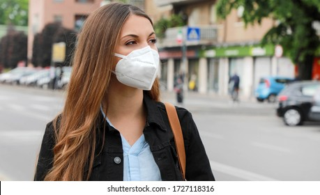 COVID-19 Pandemic Coronavirus Woman in city street wearing KN95 FFP2 mask protective for spreading of disease virus SARS-CoV-2. Girl with protective mask on face against Coronavirus Disease 2019.