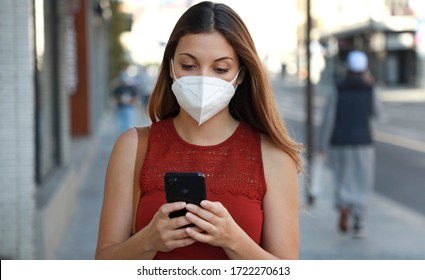 COVID-19 Pandemic Coronavirus Young Woman Wearing KN95 FFP2 Mask Using Smart Phone App in City Street to Aid Contact Tracing in Response to the 2019-20 Coronavirus Pandemic