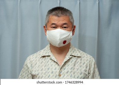 COVID-19 Pandemic - Front view portrait of middle aged Asian man wearing DIY homemade surgical face mask with Japan flag. Coronavirus protection. Indoors.