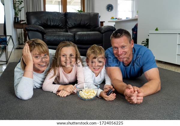 COVID-19 pandemic - lockdown. Happy caucasian family together at home having fun watching TV while schools are closed due to coronavirus. Stay Home, Stay Safe keep social distancing.