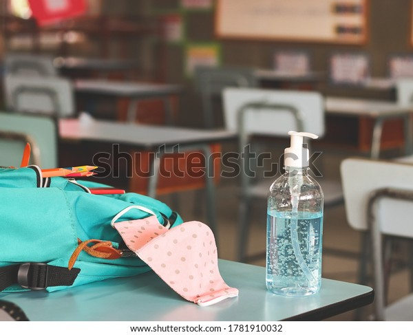 COVID-19 prevention , back  to school  and new normal  concept.Front view of  sanitizer hand gel , pink polka dots fabric mask  and  backpack with school supplies on  school desk in classroom.