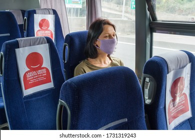 COVID-19 Public bus traveling during the coronavirus pandemic. Woman wearing protective mask while traveling by bus with new social distancing protect rules during pandemic of coronavirus in Italy